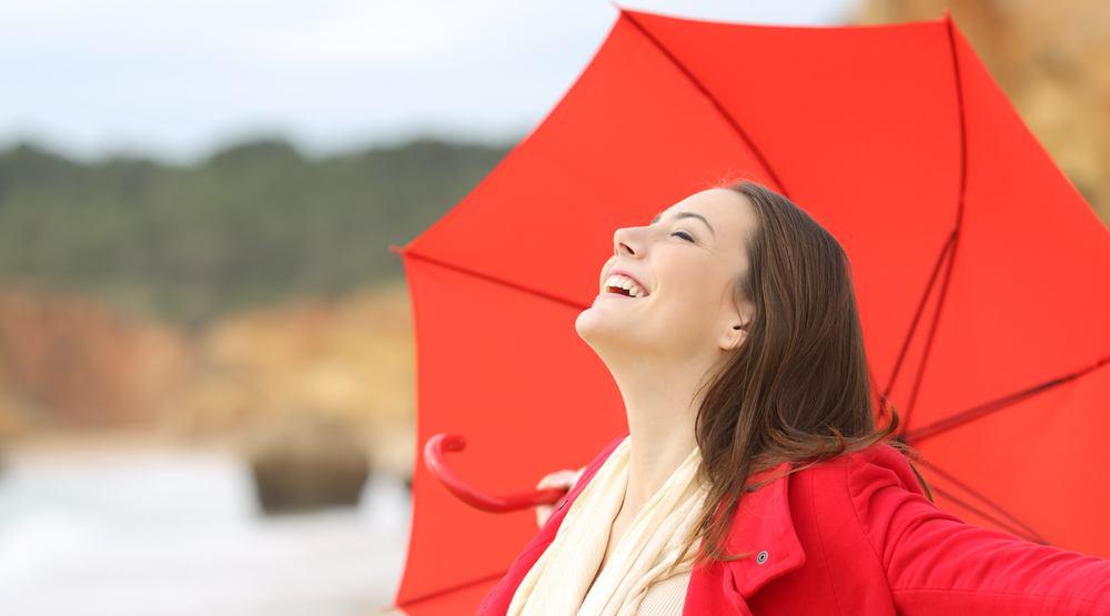 Woman with umbrella in rain and sun antonio guillemshutterstock