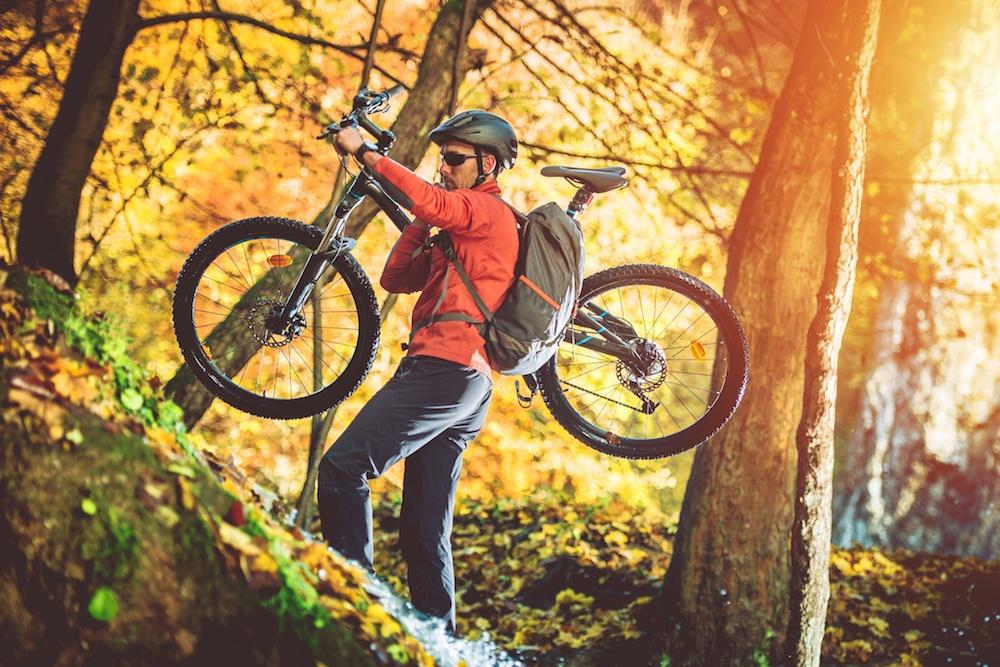 mountain biker carrying his bike up the trail (welcomia/Shutterstock)