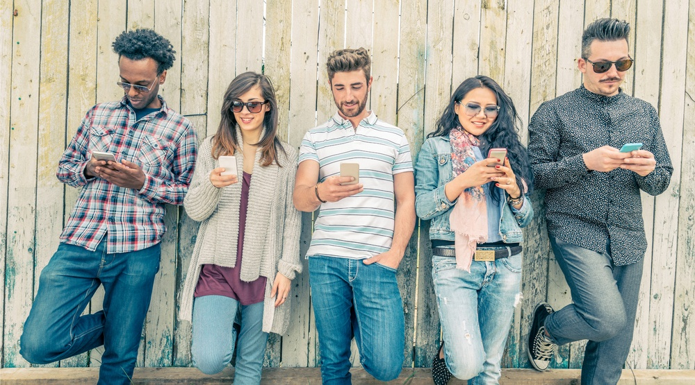 Group of hipsters leaning on a wall (oneinchpunch/Shutterstock)
