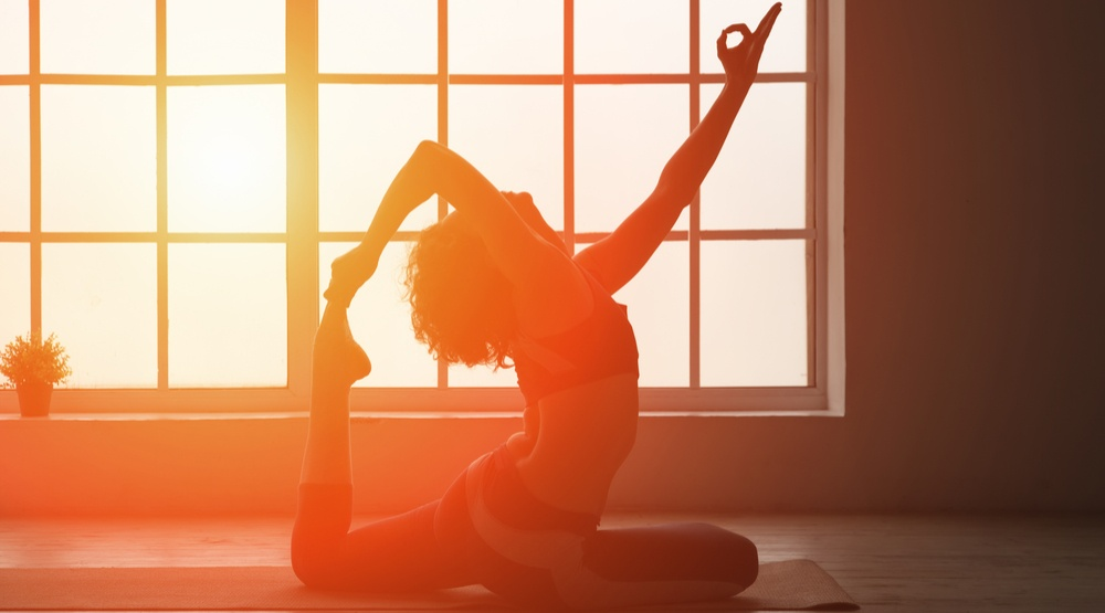 Woman doing yoga indoors in the sunset a stockstudioshutterstock