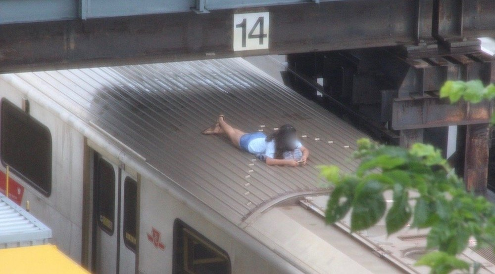 Young woman caught hanging out on top of a subway at Davisville Station