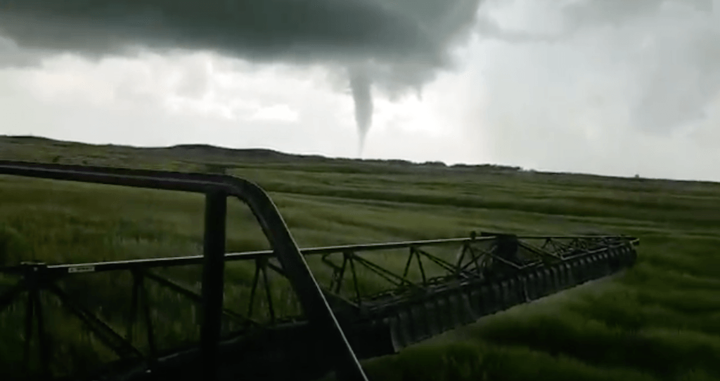 Canadian man continues to spray crops despite nearby tornado (VIDEO)