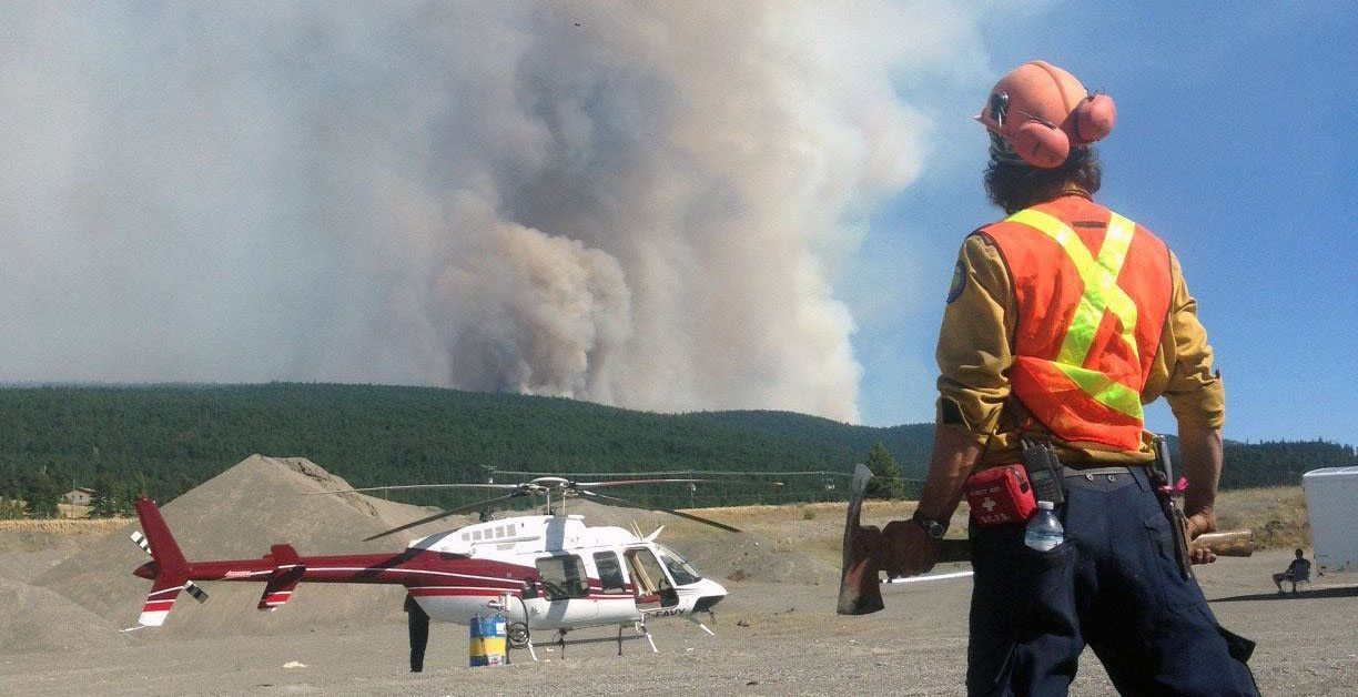 A firefighter and helicopter at the elephant hill wildfire burning in bc bc wildfire service facebook