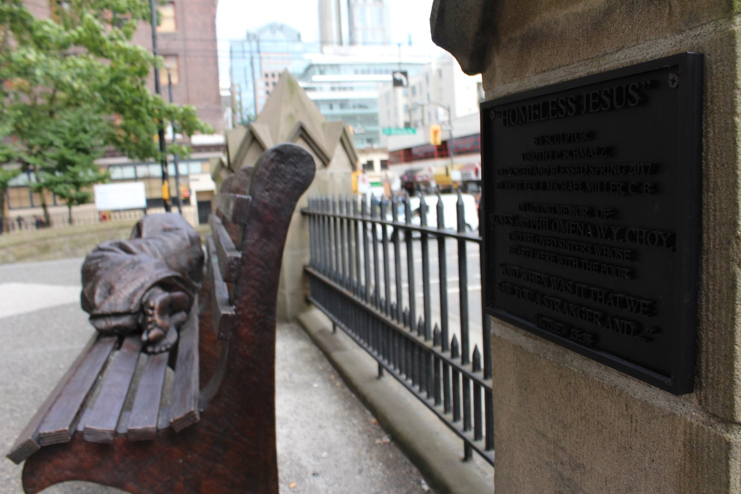 """The plaque reads: """"Homeless Jesus"""" by sculpture Timothy P. Schmalz, dedicated and blessed spring 2017 by most rev J Michael Miller, C B. In loving memory of Agnes and Philomena W. Y. Choy, two beloved sisters whose hearts were with the poor. """"And when was it that we saw you a stranger and..."""" Matthew 25:36 (Chandler Walter/Daily Hive)"""