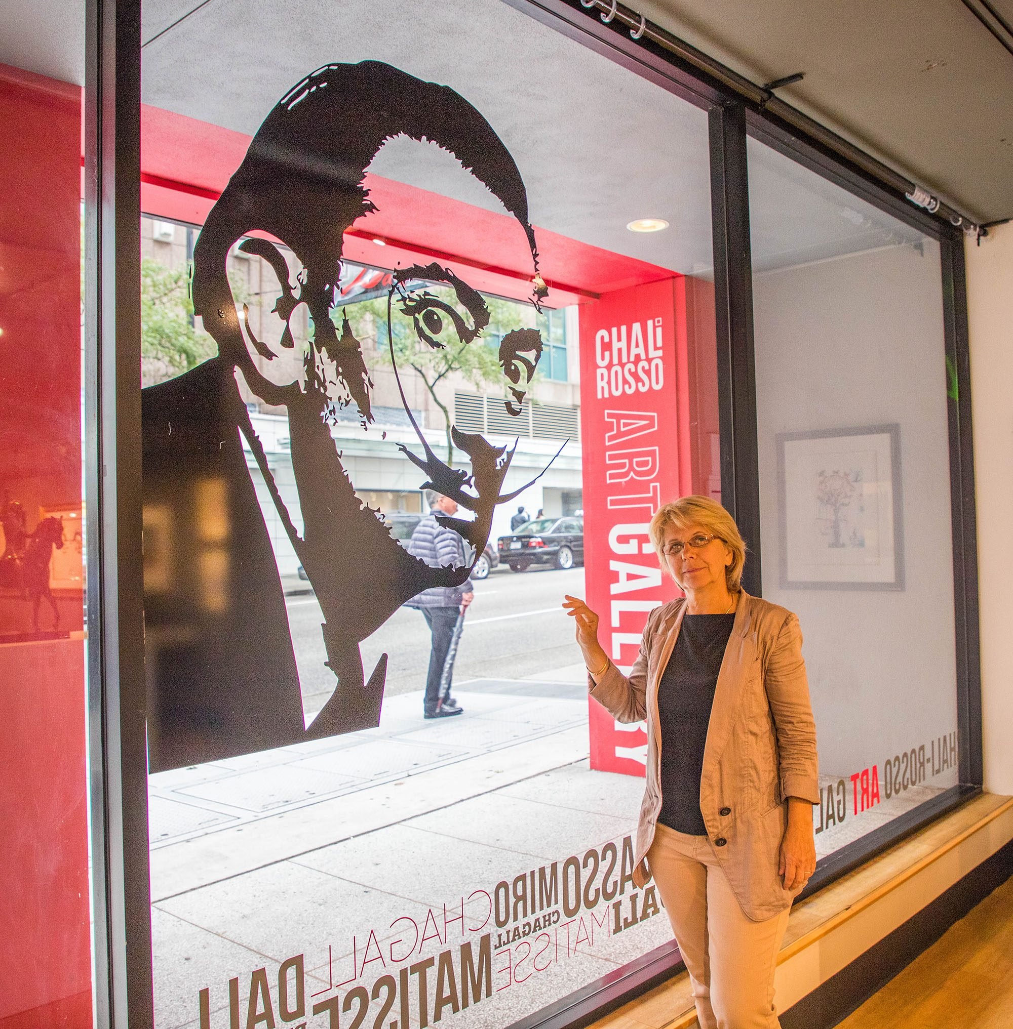 Susanna Strem, Chali-Rosso Gallery owner, and Salvador Dalí print (Jenni Sheppard/Daily Hive)