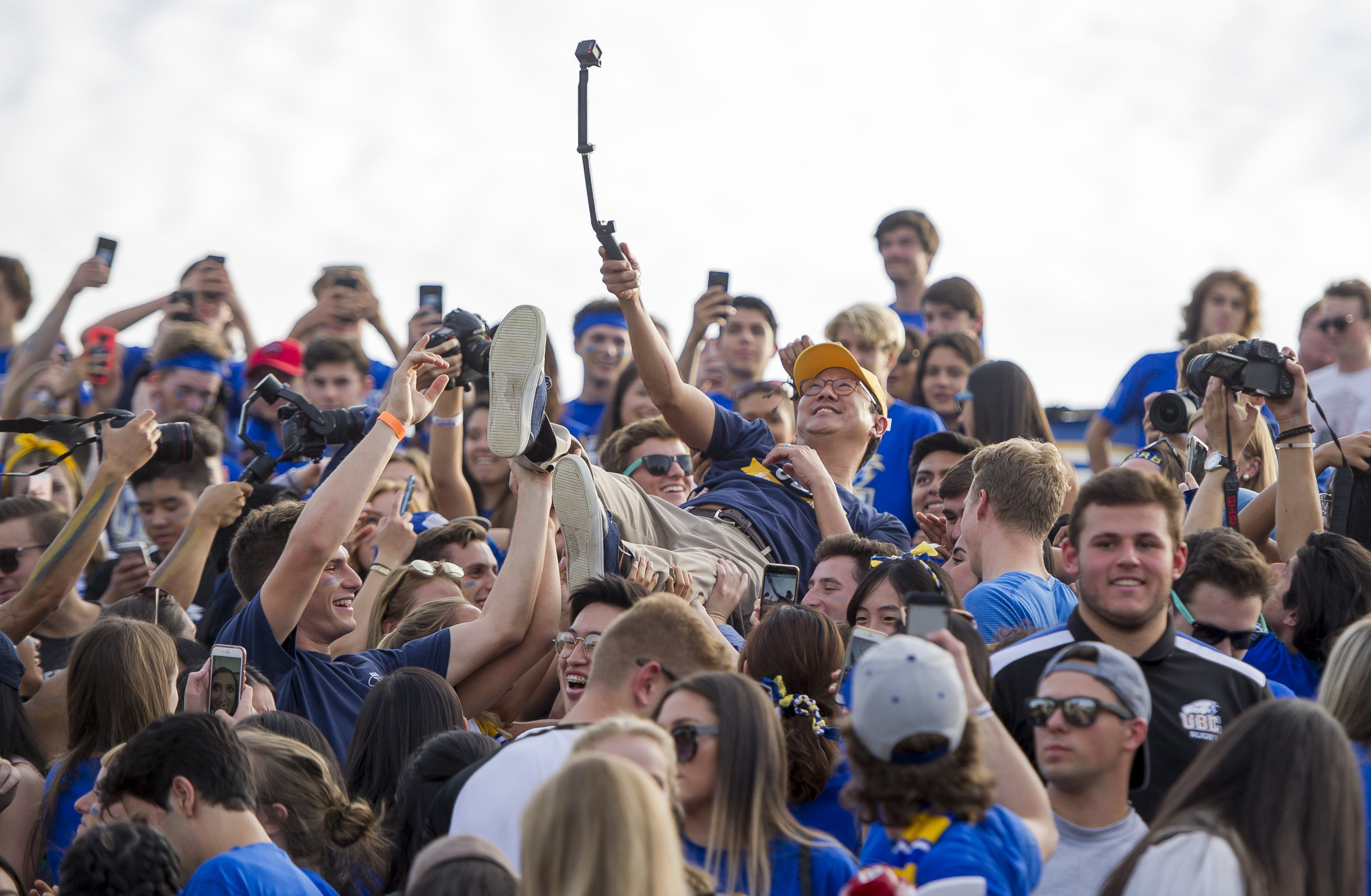 UBC's awesome president goes crowd surfing at football game (PHOTOS)