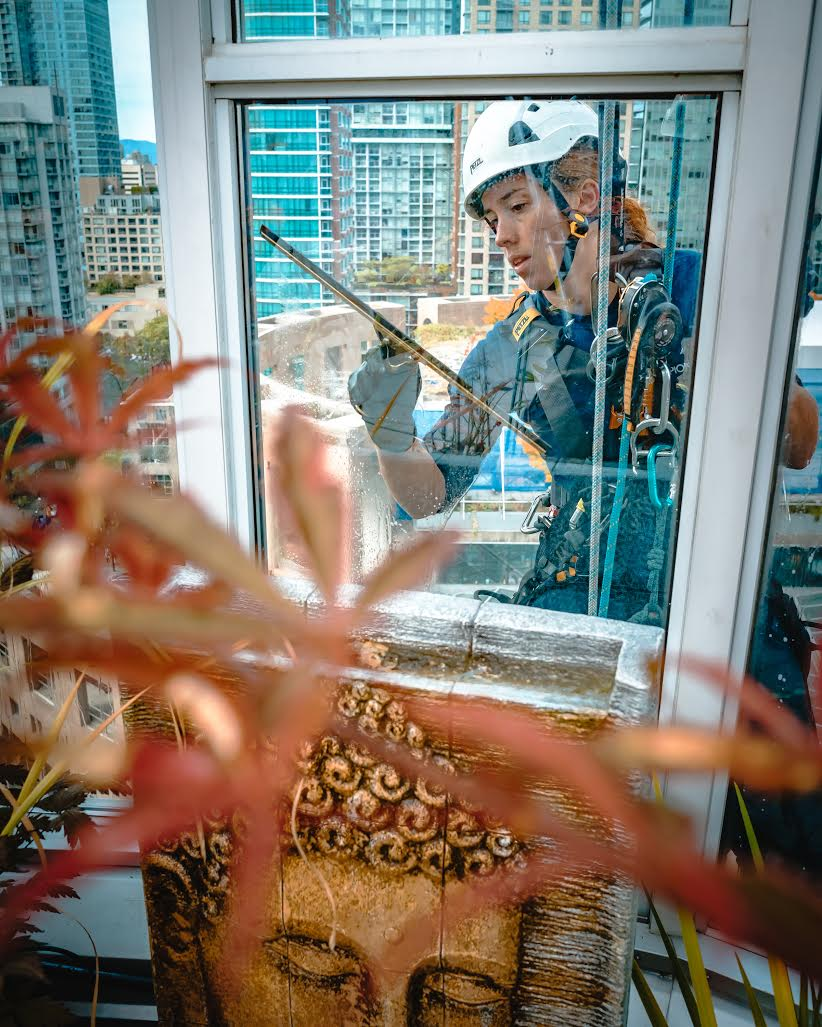 Dominica Myles cleaning windows on a high-rise building (Nicolas Guaiquin)