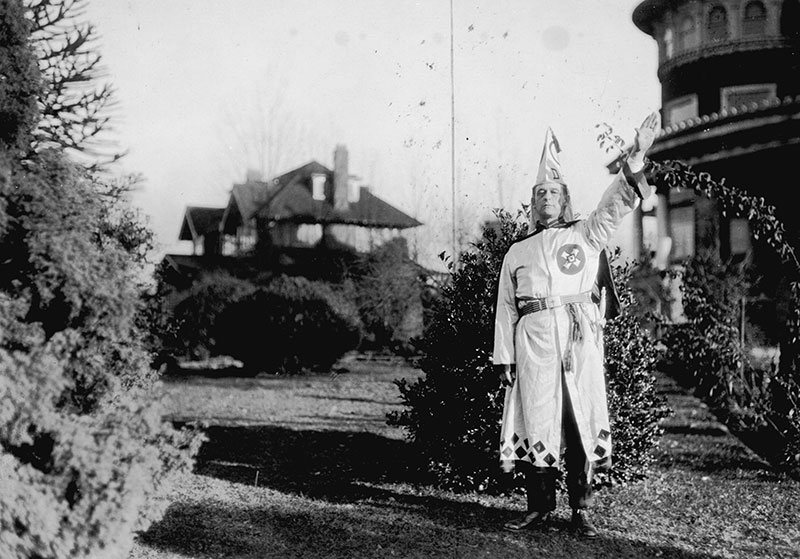 Ku Klux Klan member outside their Shaughnessy headquarters at Glen Brae Manor in 1925. Photo by Stuart Thomson, City of Vancouver Archives #99-1499.