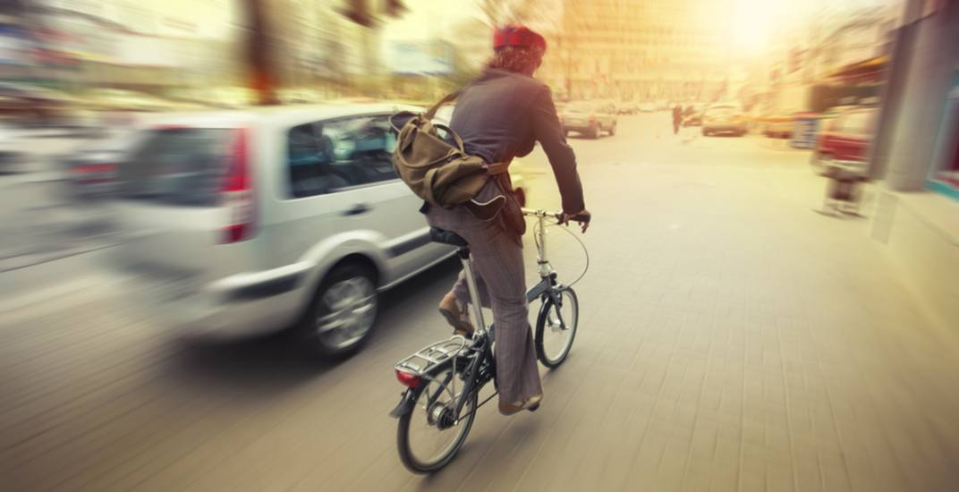 Cyclist in traffic with cars rocksweepershutterstock