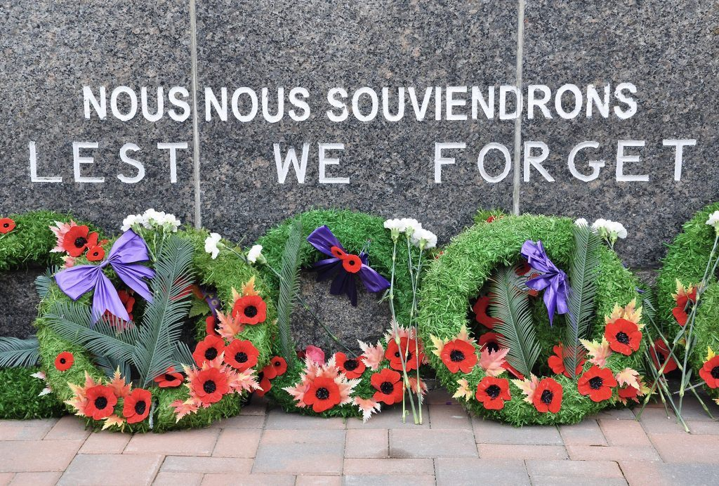 Remembrance Day wreaths in front of a Lest We Forget engraving (Lester Balajadia/Shutterstock)