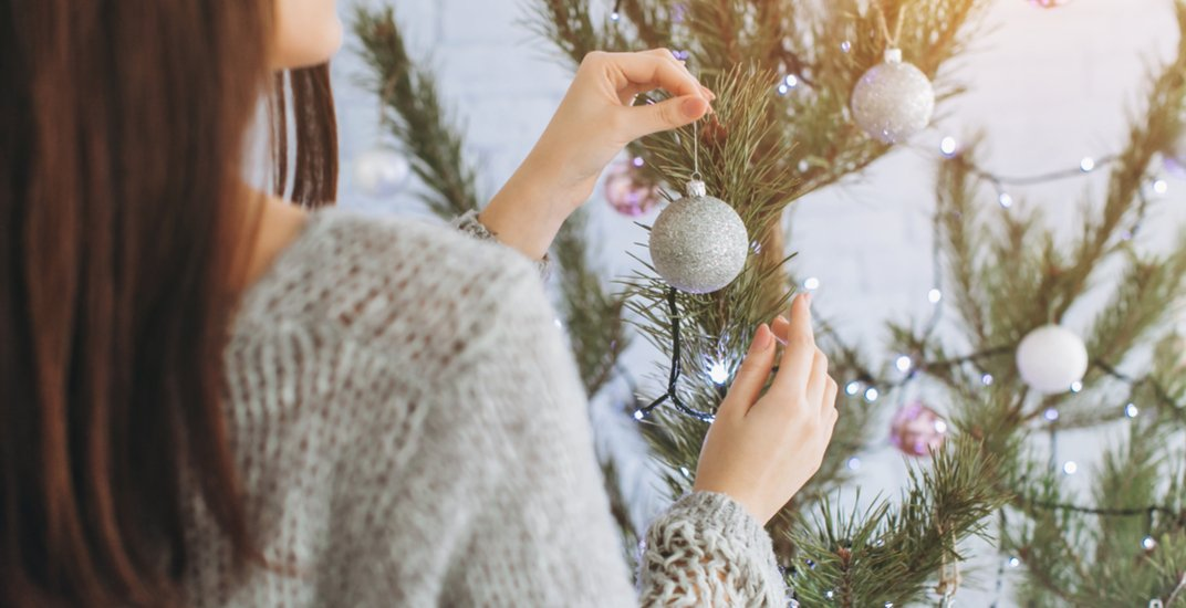 Girl decorating a Christmas tree / Shutterstock