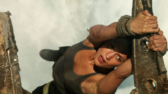 Lara Croft pulling herself up onto rusty plane debris.