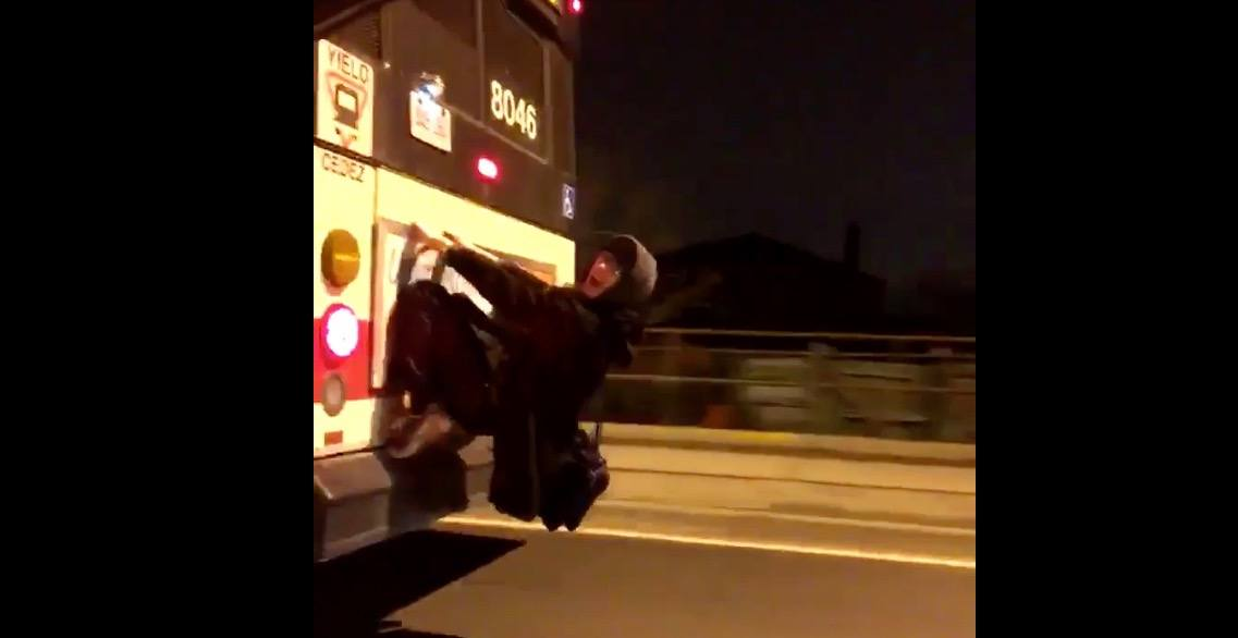 Man captured riding dangerously on back of TTC bus (VIDEO)