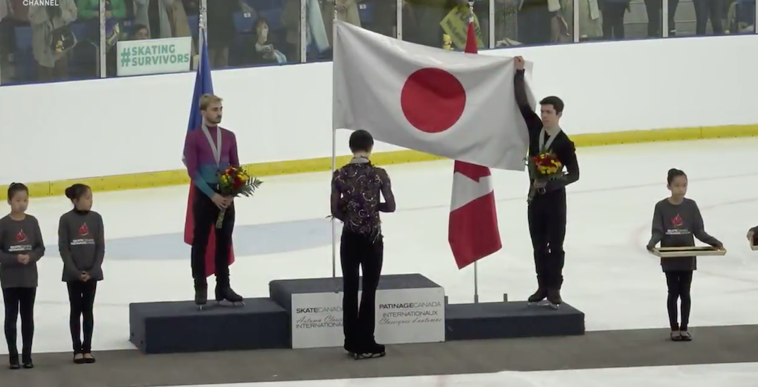 Canadian figure skater Keegan Messing holds Japanese flag for competitor during national anthem