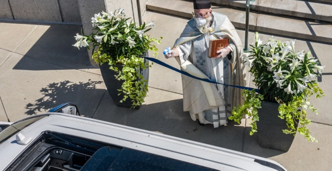 Detroit priest uses water gun to spray Holy Water for distancing (PHOTOS)