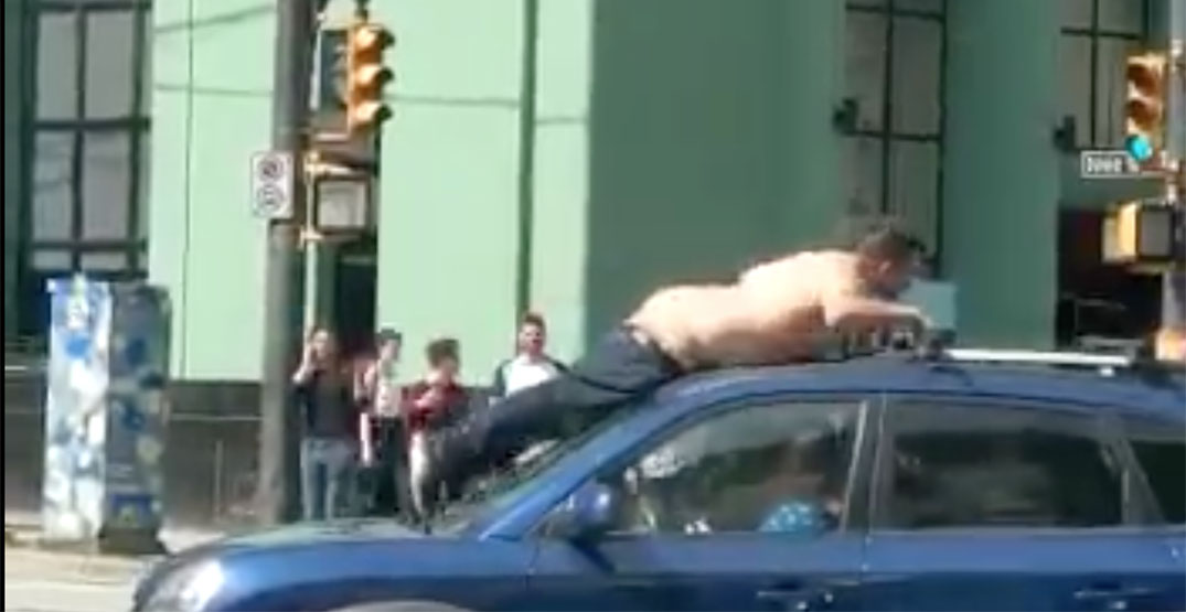 Nearly-naked man climbs on car in downtown Vancouver intersection