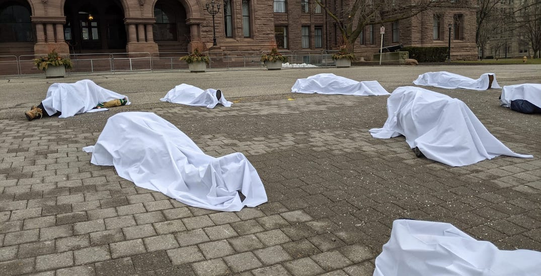 Healthcare workers stage die-in protest outside Queen's Park