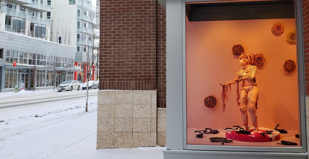 Visit a sculpture covered with flowers and snakes in this Inglewood window