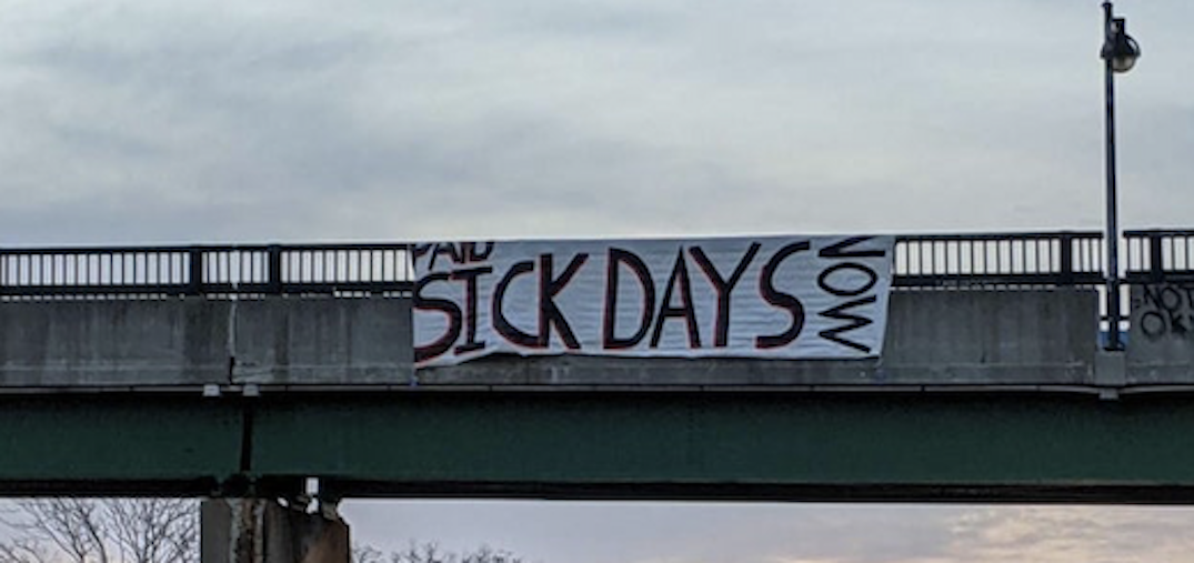 Banner demanding paid sick days hung over the Gardiner Expressway this morning
