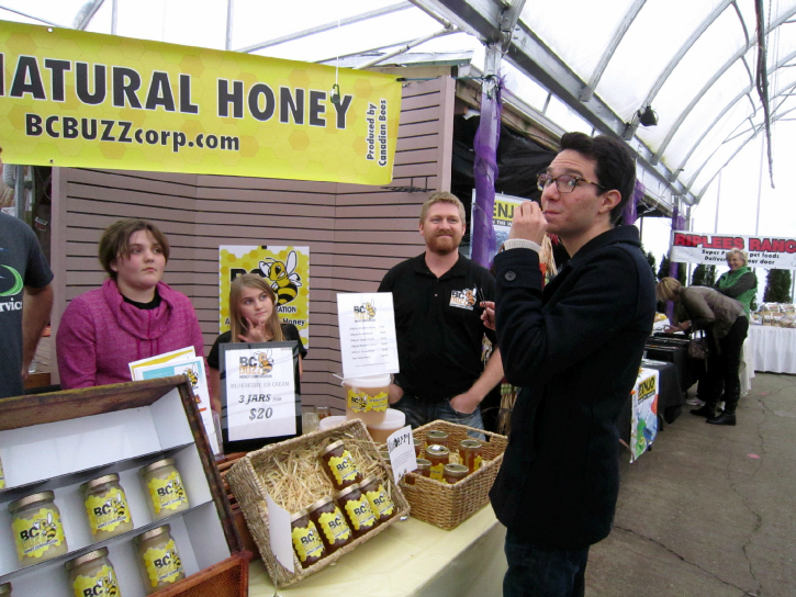 This Vancity Buzz writer sampling some delicious BC Buzz honey at the Milner Village Market.