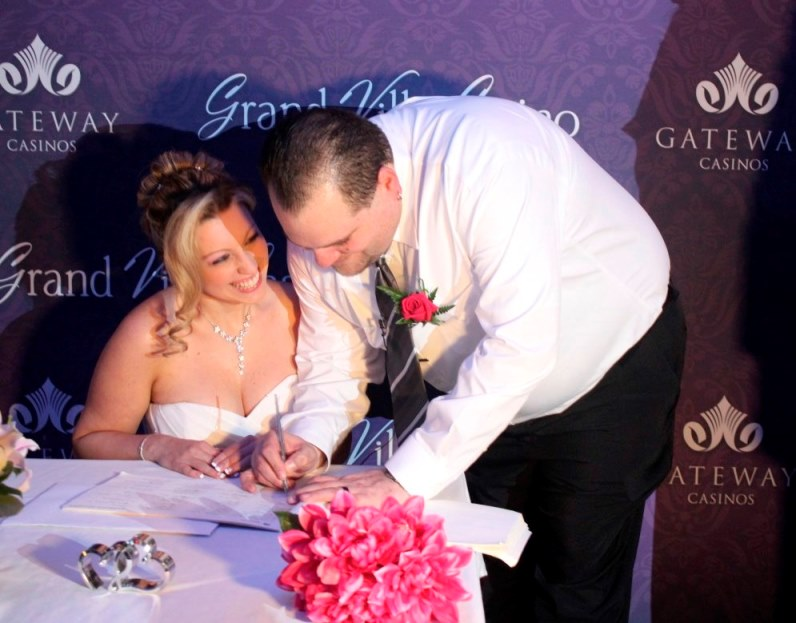 Jim signs the papers while Danielle smiles