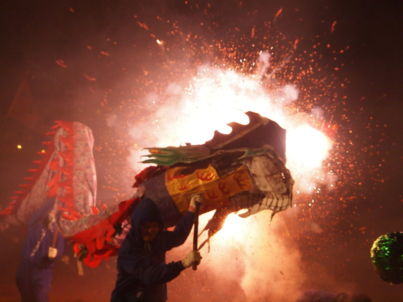 Chinese New Year dragon dance firecrackers / Shutterstock