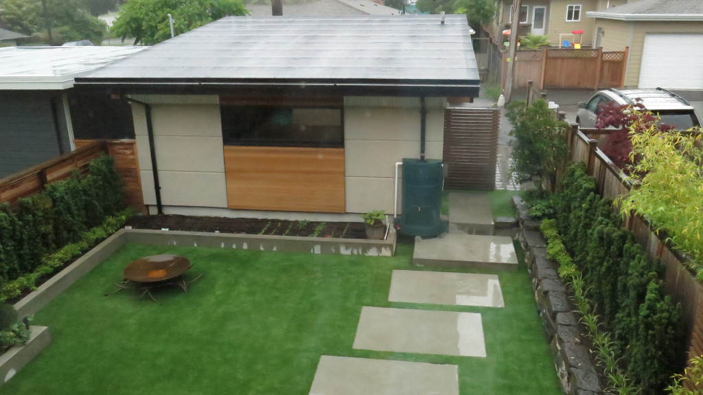 Image: Shed showcasing a green water recollection tank that serves the permeable landscaping.