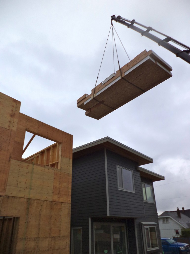 Image: During construction the lowering of the structural insulating panel (SIP) roof system.