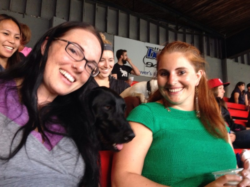 Caitlin and Jax hang out with a very happy black dog.