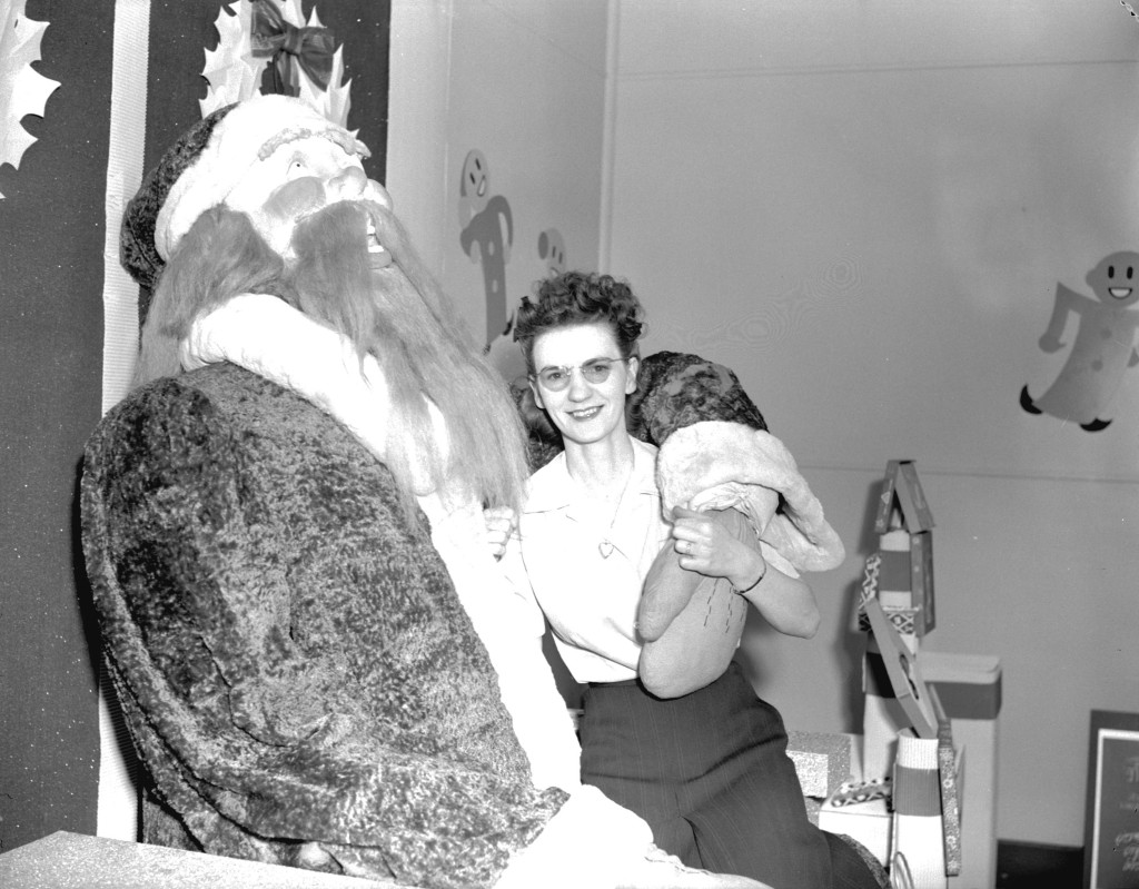 Hudson Bay Company woman sitting with display Santa, 1943. Photo via Vancouver Archives.