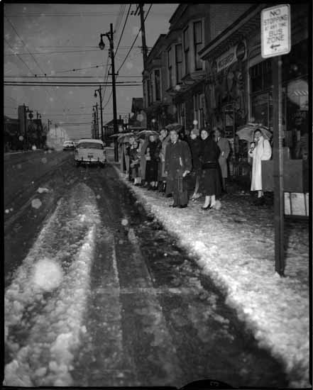 People wait for a bus on Denman Street