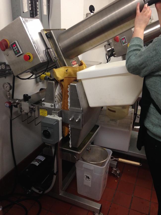 Feeding the X-1 cold press machine (Lindsay William-Ross/Vancity Buzz)