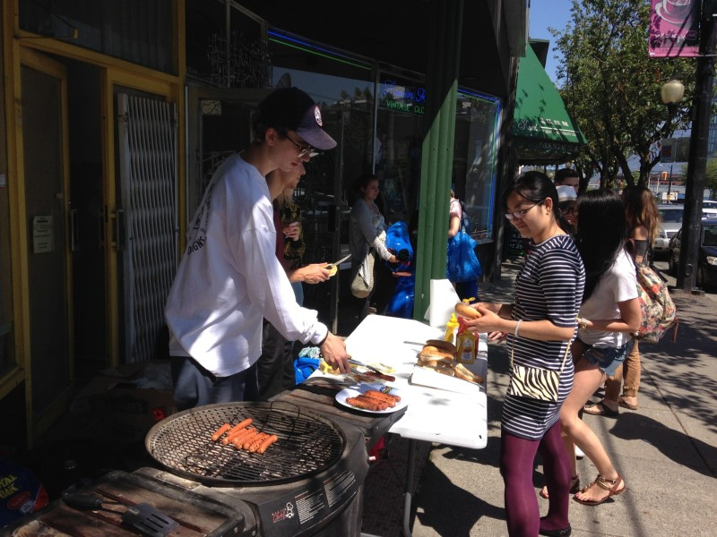 An employee cooks hotdogs and veggie dogs in front of the store on Main Street/Photo: Lauren Sundstrom