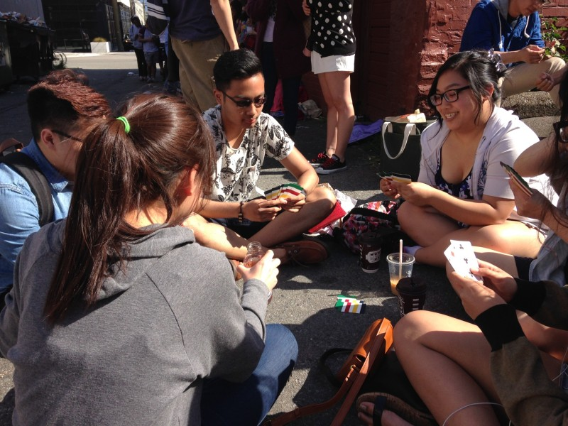 A group of people play cards to pass the time. They've been waiting in line since 7:30 a.m./Photo: Lauren Sundstrom