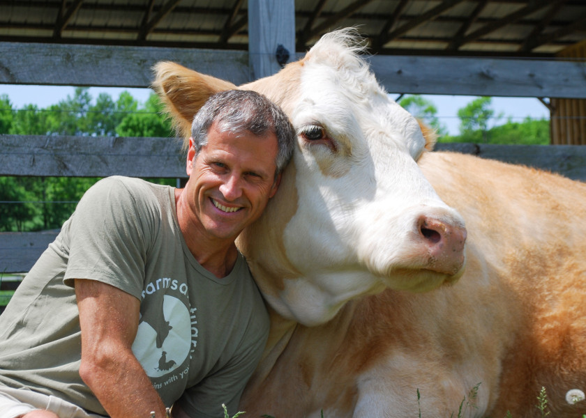 Gene and a Farm Sanctuary resident (Farm Sanctuary).
