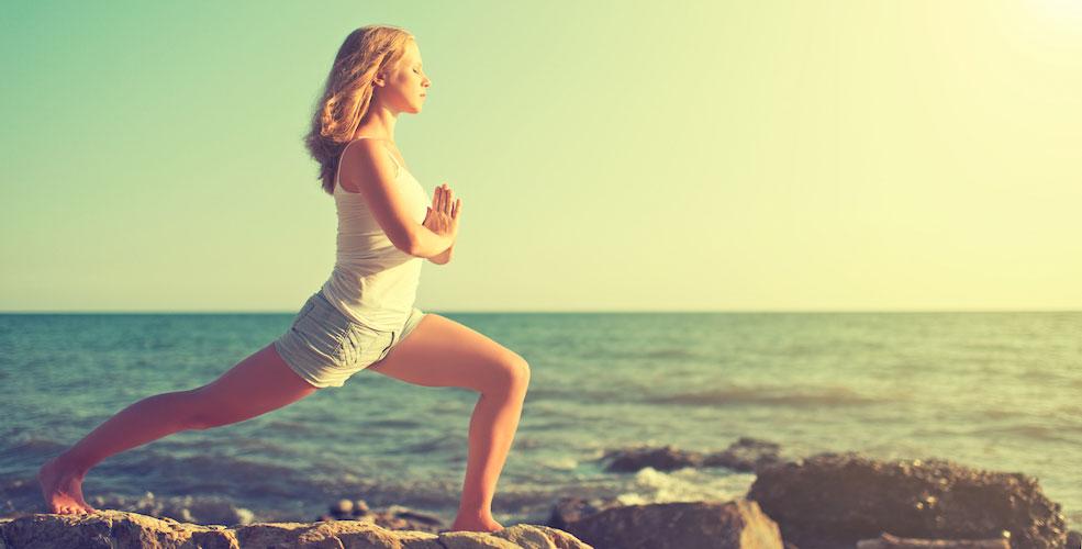 Young woman doing yoga on coast of sea of beach