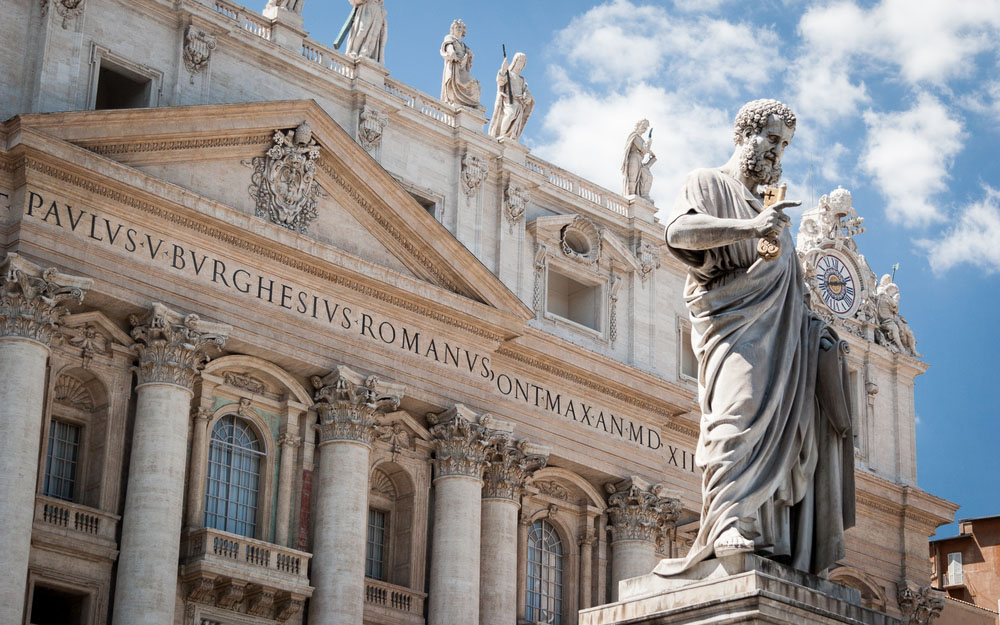 Low angle view of the statue of St. Peter in St. Peter's Square, Vatican City, with the front of the famous Basilica in the background. (pxl.store/Shutterstock)