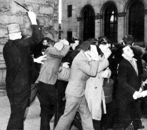 Plain-clothes police officer beating demonstrators with billy clubs during the post office riot on Bloody Sunday in 1938. (B.C. Archives)