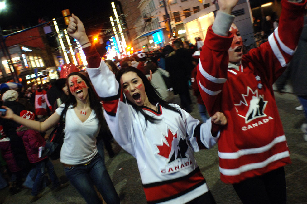 Canadian hockey fans celebrate on the streets of Vancouver after Team Canada won gold at the 2010 Winter Olympic Games on February 28, 2010 (Sergei Bachlakov/Shutterstock)